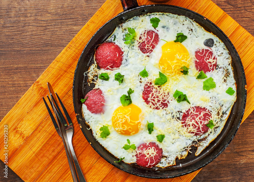fried egg with ham sausage and cheese in a frying pan on wooden table background