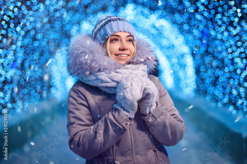 Young beautiful pretty woman smiling and posing at city street with snowflakes Christmas lights bokeh outdoor at night time.