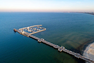 Sopot resort near Gdansk in Poland. Wooden pier with harbor, marina with yachts and beach. Aerial view in sunset light. Far view of Gdansk in the background