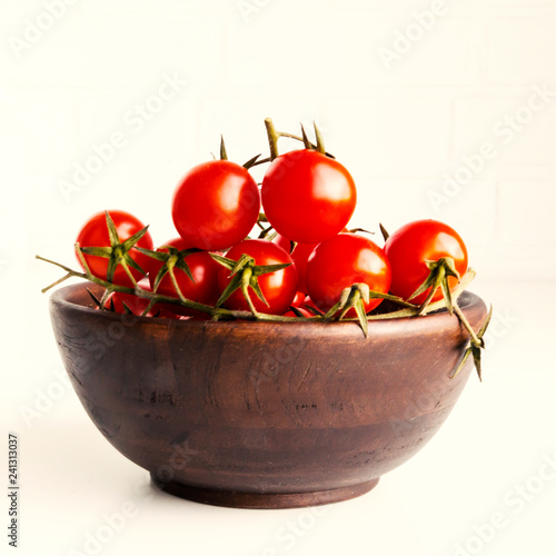Red fresh cherry tomatoes in wooden bowl. Closeup.