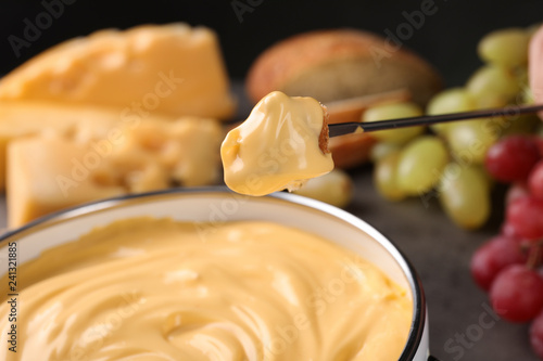 Piece of bread over pot with delicious cheese fondue, closeup - 241321885
