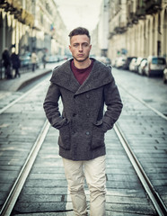 Attractive young man standing in the middle of city street looking at camera