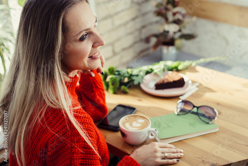 Happy woman enjoying some coffee in a cafeteria - 241327097