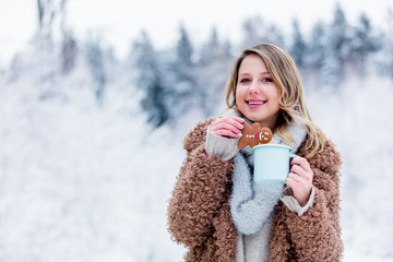 Beautiful girl in coat with cup of hot drink and cookie in a snow forest. Christmas of Valentine Day season time © Masson