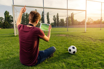 Back view, teenager soccer fan watching live stream of game on soccer pitch