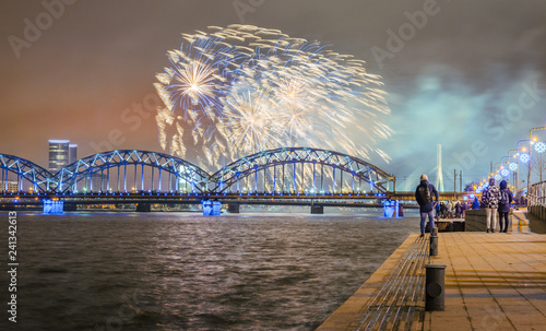 New Year's evening with colorful fireworks in Riga over river Daugava. Railroad bridge with colorful reflections from fireworks.