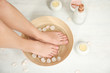 Leinwanddruck Bild - Woman soaking her feet in bowl with water and rose petals on floor, top view. Spa treatment