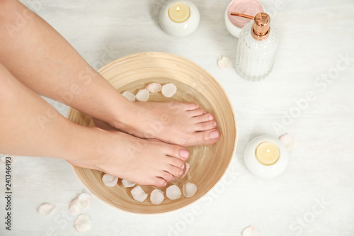 Leinwanddruck Bild Woman soaking her feet in bowl with water and rose petals on floor, top view. Spa treatment