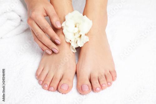 Leinwanddruck Bild Woman touching her smooth feet on white towel, closeup. Spa treatment