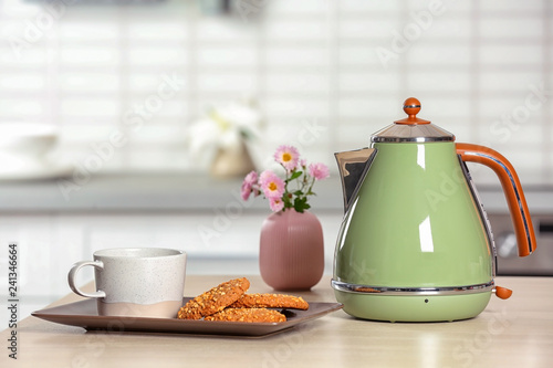Leinwanddruck Bild Stylish electrical kettle, cup and cookies on table against blurred room interior. Space for text
