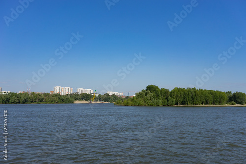 urban landscape with views of the Ob river and coastline with houses against a blue sky.