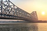Howrah bridge Kolkata on river Ganges at sunrise with winter haze. Howrah bridge is one of the busiest cantilever bridge in India