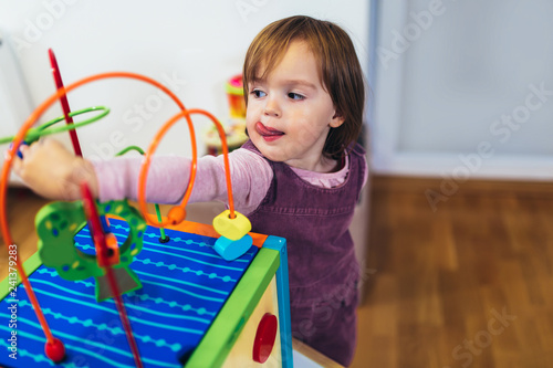 Cute child playing on table indoor - 241379283