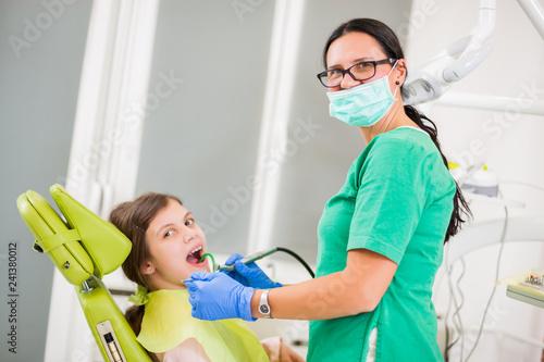 Dentist is repairing teeth of little girl. - 241380012