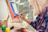 Elderly woman is painting in her home. Retirement hobby.  - 241381411
