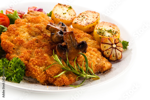 Leinwandbild Motiv Fried pork chop with potatoes on white background