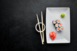 Sushi roll maki with salmon. Japanese cuisine. Top view. On a black stone background.
