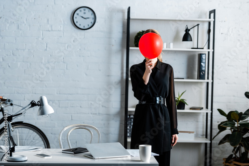 businesswoman in black clothes standing near table and hiding face behind red balloon