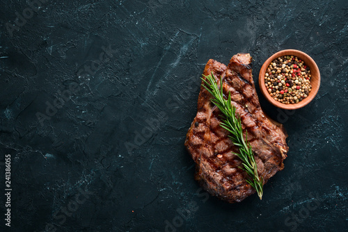 Veal steak on a bone on a black background. Free space for your text. Top view. - 241386055