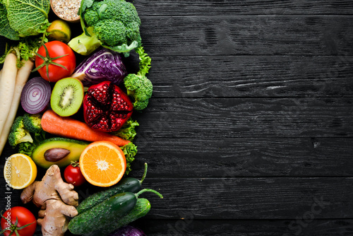 Fresh vegetables and fruits. Organic food on a black wooden background. Top view. Free copy space. - 241386675