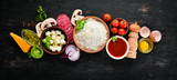 Ingredients for pizza. Mushrooms, sausages, tomatoes, vegetables. Top view. On a black wooden background. Free copy space. - 241387657