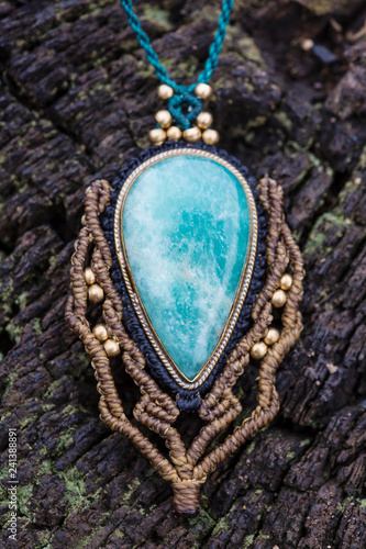 Amazonite stone macrame ornamental pendant on wooden background - 241388891