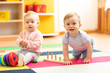 Leinwandbild Motiv crawling funny baby boy and girl in play room in nursery