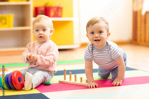 crawling funny baby boy and girl in play room in nursery