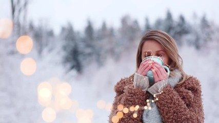 Footage of Beautiful girl in coat with cup of hot drink in a snow forest. Christmas of Valentine Day season time © Masson