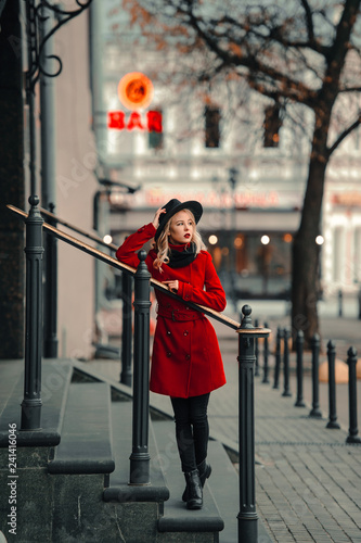 obraz lub plakat young blond girl walk in the street in red coat