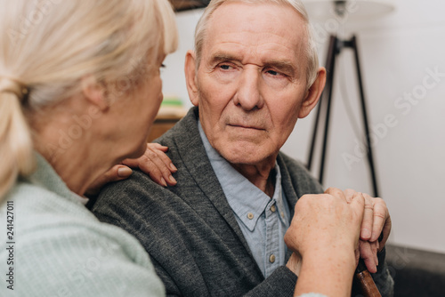 Foto Murales selective focus of sad pensioner looking at retired wife at home