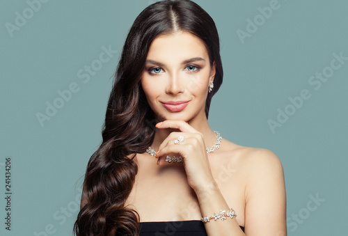 Happy girl with jewelry. Brunette woman with makeup and curly hairstyle and diamond necklace on blue background