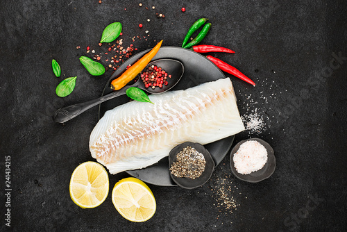 Cod fillets on a black ceramic plate for the preparation of a healthy dish with the addition of pink pepper, hot pepper, spinach, lemon, salt on a simple black background. Top view. Copy space - 241434215