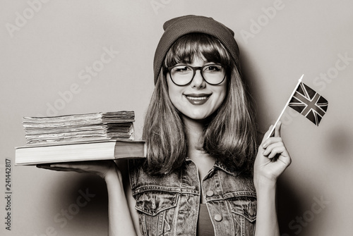 Leinwanddruck Bild Portrait of young style hipster girl with Great Britain flag in hand and books . Image in black and white color style