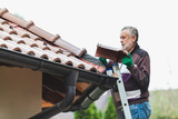 man repairs tiled roof of  house close up - 241447804