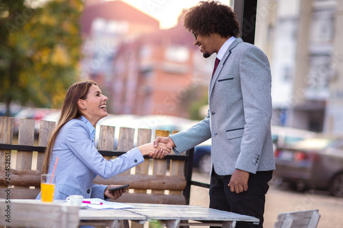 Businesswoman and businessman handshake in the cafe. - 241452851