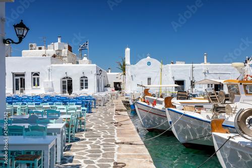 Leinwanddruck Bild Die Hafenpromenade mit Restaurants und Tavernen direkt neben den Fischerbooten in Naousa, Paros, Kykladen, Griechenland