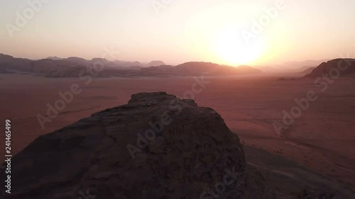 Drone flying over desert mountains with adventure 4WD off road cars parked in sand at sunset