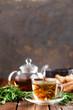 Leinwanddruck Bild - Rosemary tea in glass tea cup on rustic wooden table closeup. Herbal vitamin tea.