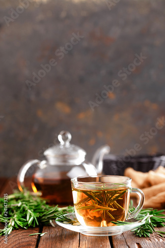 Rosemary tea in glass tea cup on rustic wooden table closeup. Herbal vitamin tea.