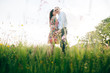 Leinwanddruck Bild - Beautiful young couple gently hugging  in sunshine in fresh spring meadow with pink flowers. Happy stylish family embracing in green field in sunlight. Romantic moments. Hello Spring
