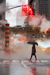 A woman with an umbrella and red high heels shoes is crossing the 42nd street in Manhattan. Taxi and steam coming out from from the manholes in the background. New York City, Usa.