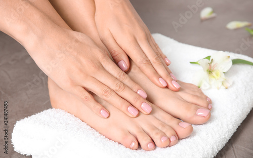 Leinwanddruck Bild Woman touching her smooth feet and towel on grey background, closeup. Spa treatment