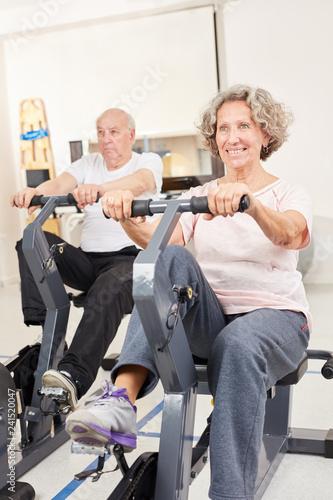 Senioren Paar trainiert auf dem Ergometer - 241520047