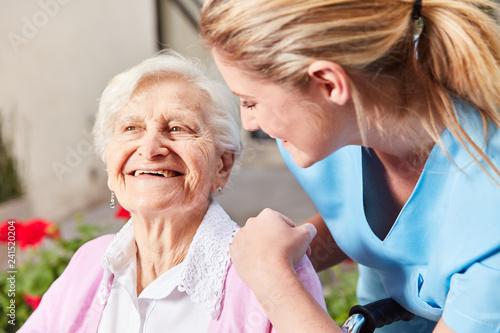 Leinwandbild Motiv Altenpflegerin kümmert sich um Senior Frau