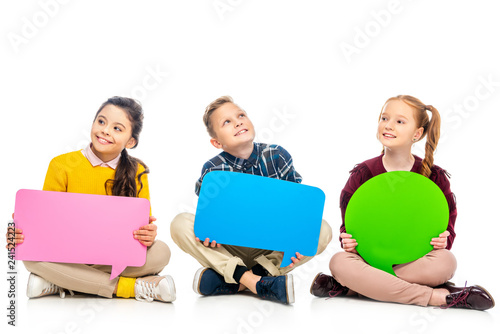 cheerful kids sitting and holding multicolored speech bubbles isolated on white