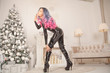 latex rubber skinny evil woman with pink bdsm riding crop posing on white background with christmas tree and fireplace with new year decorations