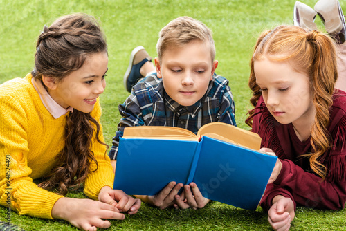 cute kids lying on lawn and reading book