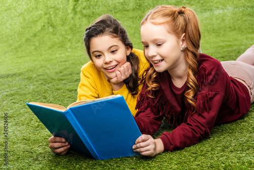 cheerful schoolgirls lying on lawn and reading book