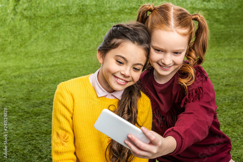 cute schoolgirls smiling and taking selfie on lawn